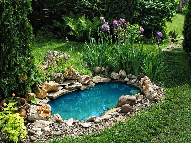 Отделка озера на лужайке природным камнем