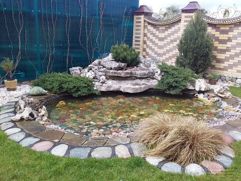 Декорирование водоема на лужайке известняком
